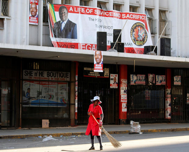 A woman sweeps the street outside the opposition Movement for Democratic Change (MDC) headquarters in Harare