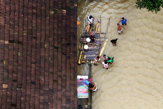 People wait for aid next to makeshift raft at a flooded area in the southern state of Kerala