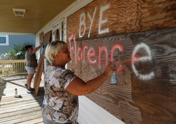 Lisa Evers and her daughter Amanda Hamilton, both of Oak Island, decorate their storm shutters before evacuating ahead of the arrival of Hurricane Florence in Oak Island