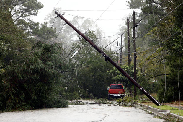 A utility pole leans precariously over a street littered with downed trees and branches after Hurricane Florence swept through Wilmington