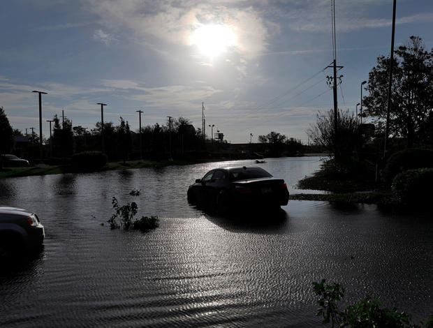 The sun reflects on flood water and stranded vehicles as it emerges after days of storm clouds and rain, in the aftermath of Hurricane Florence in Wilmington, North Carolina