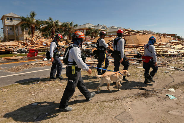 Search and rescue crews walk past damage caused by Hurricane Michael in Mexico Beach