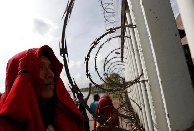 Migrants, part of a caravan trying to reach the U.S., stand in front of the fortified border gate between Guatemala and Mexico, in Tecun Uman