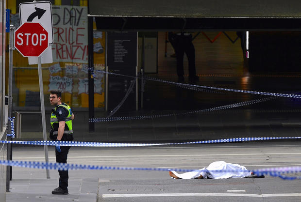 A policeman stands near a body covered with a sheet near the Bourke Street mall in central Melbourne