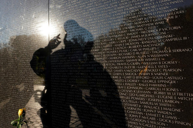 A visitor is reflected in the Vietnam Veterans Memorial wall on Veteran's Day in Washington
