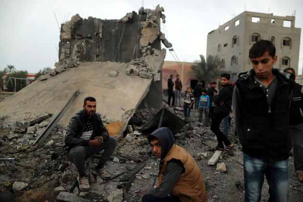 Palestinians sit at the remains of a building that was destroyed by an Israeli air strike, in Khan Younis in the southern Gaza Strip
