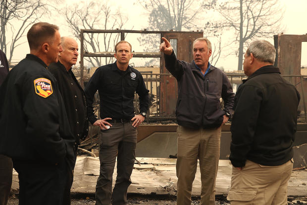 California Gov. Jerry Brown, second left, FEMA Administrator Brock Long, center left, and U.S. Secretary of the Interior Ryan Zinke, center right, tour a school burned by the Camp Fire on Nov. 14, 2018, in Paradise, California.