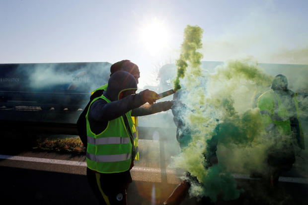 People wearing yellow vests, a symbol of French drivers' nationwide protest against higher fuel prices, block the Paris-Brussels motorway in Haulchin