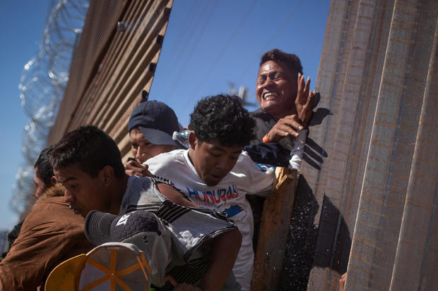 Migrants are hit by tear gas after attempting to illegally cross the border wall into the U.S. in Tijuana, Mexico