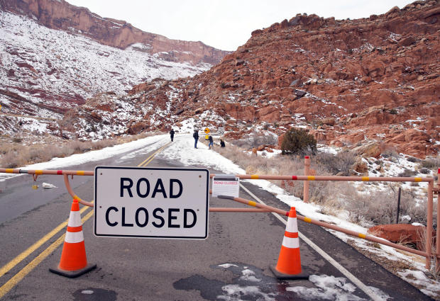 Hikers walk up the main road, which is closed because of the partial government shutdown, in Arches National Park, Utah