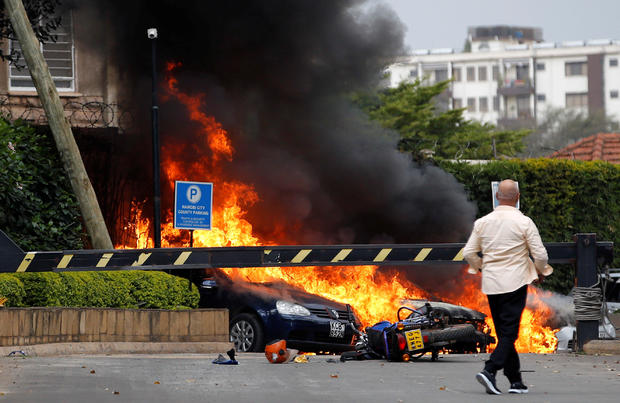 Cars are seen on fire at the scene where explosions and gunshots were heard at the Dusit hotel compound, in Nairobi