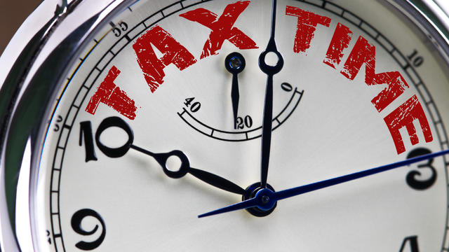tax time concept clock closeup isolated on white background with red words