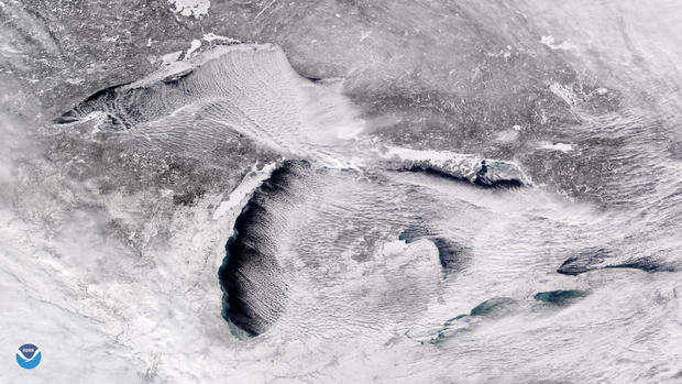 """Handout photo of a satellite image taken over the Great Lakes showing rows of cumulus clouds also known as """"cloud streets"""" streaming over the lakes' surface, caused by the frigid weather"""