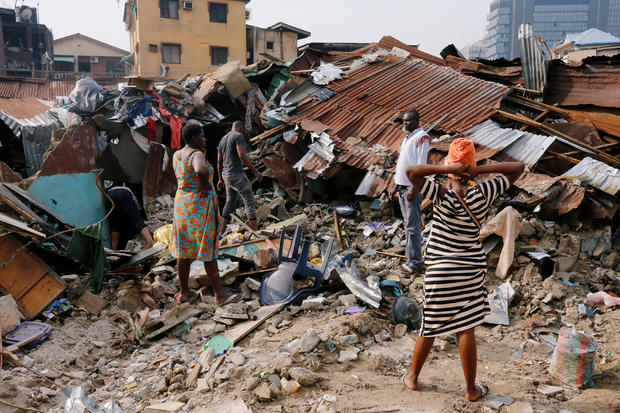 A woman searches for belongings at the site of a collapsed building in Nigeria's commercial capital of Lagos