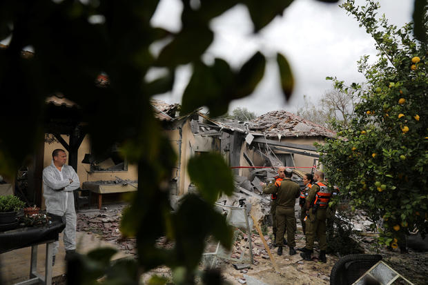 An Israeli police sapper and soldiers work next to a house that was hit by a rocket north of Tel Aviv, Israel
