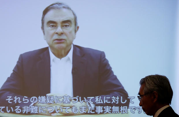 Junichiro Hironaka, chief lawyer of the former Nissan Motor chairman Carlos Ghosn, walks in front of a screen showing Ghosn's video statement during a news conference at Foreign Correspondents' Club of Japan in Tokyo