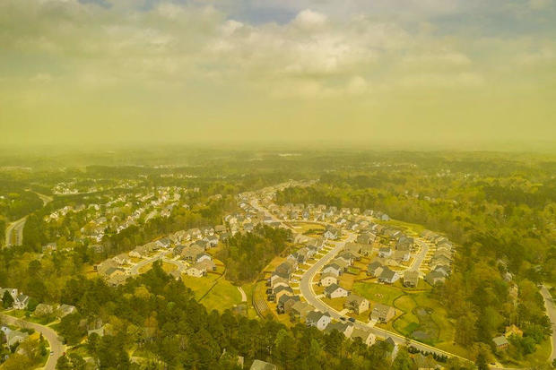 An aerial view shows pollen haze tinting the environment yellow over an area in Durham, North Carolina