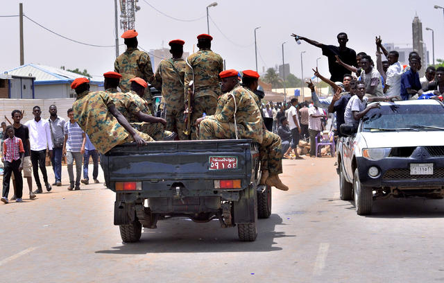 Sudanese demonstrators cheer as they drive towards a military vehicle near Defence Ministry in Khartoum