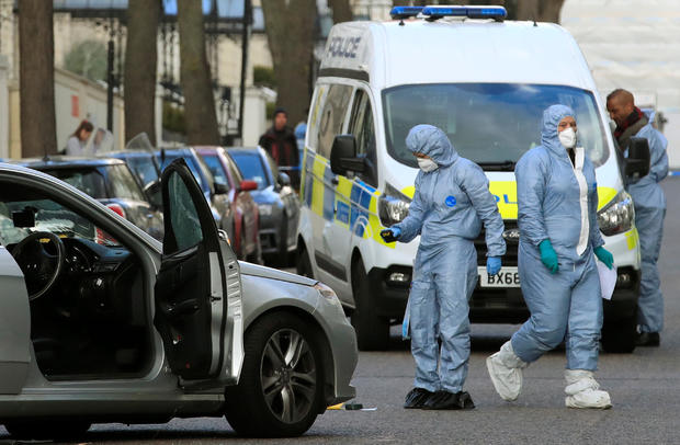 Police forensics officers work at the site where police fired shots after a vehicle rammed the parked car of Ukraine's ambassador, outside the Ukrainian embassy in London