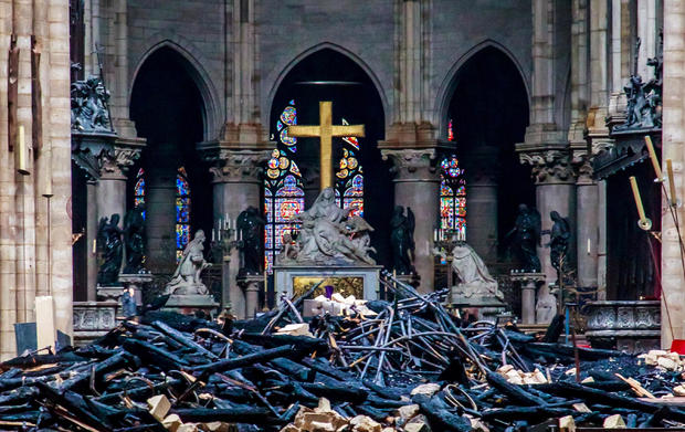 The cross and sculpture of Pieta by Nicolas Coustou are seen surrounded by debris inside Notre Dame Cathedral in the aftermath of a fire that devastated the church during a visit by French Interior Minister Christophe Castaner, not pictured, in Paris, Fra