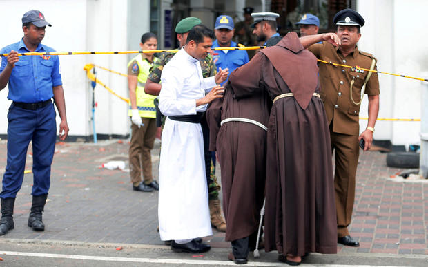 Priests walk into the St. Anthony's Shrine, Kochchikade church after an explosion in Colombo