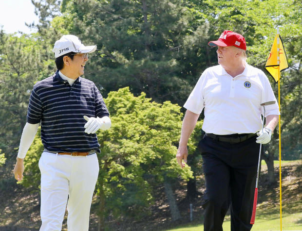 U.S. President Donald Trump talks with Japanese Prime Minister Shinzo Abe as they play golf at Mobara Country Club in Mobara, Chiba prefecture, Japan