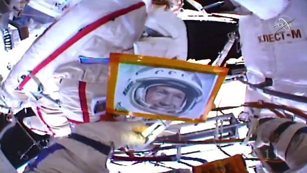 Cosmonauts Oleg Kononenko and Alexey Ovchinin floated outside the International Space Station May 29, 2019, and took a moment to call down birthday greetings to retired cosmonaut Alexey Leonov, the first man to walk in space in 1965. Carrying a portrait of Leonov outside with them, the cosmonauts both radioed best wishes to the iconic spacewalker.
