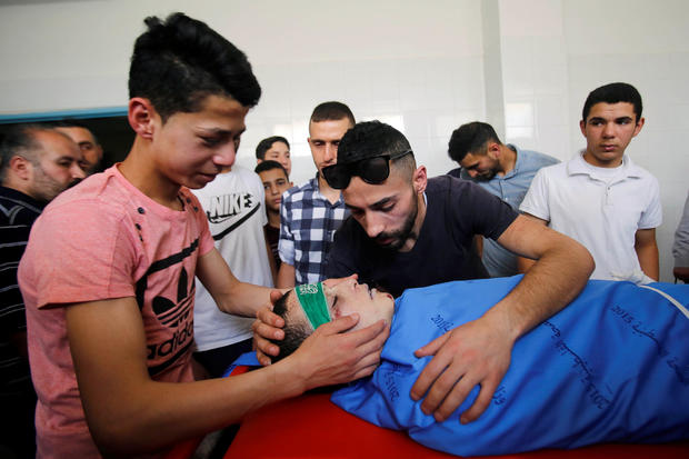 Relatives of Palestinian teenager Abdullah Ghaith look at his body at a hospital in Hebron, in the Israeli-occupied West Bank