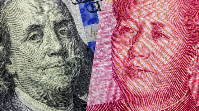 Close up of one hundred Dollar and 100 Yaun banknotes with focus on portraits of Benjamin Franklin and Mao Tse-tung/USA vs China trade war concept