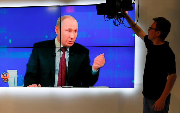 An employee works at a studio of a regional TV company during a televised phone-in show attended by Russian President Putin in Krasnoyarsk