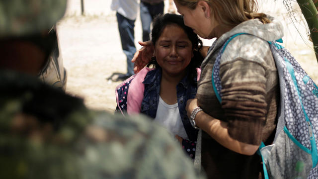 A young girl from Nicaragua is comforted by her mother after they were detained by members of Mexico's National Guard while trying to cross illegally the border between the U.S. and Mexico, in Ciudad Juarez