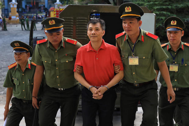 U.S. citizen Michael Nguyen is escorted by policemen before his trial at a court in Ho Chi Minh city