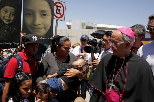 El Paso Bishop Mark Seitz chats with Honduran migrants who were deported after crossing the Paso del Norte international border crossing bridge from El Paso, Texas, U.S., in Ciudad Juarez