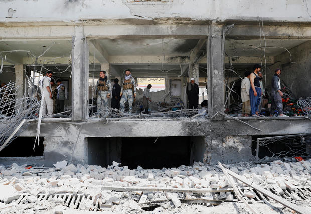 Afghan security forces inspect a damaged building at the site of a blast in Kabul, Afghanistan