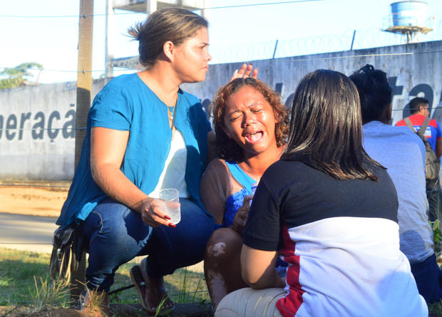 A woman cries after receiving information that her brother was one of the inmates who died during a prison riot, in front of a prison in Altamira