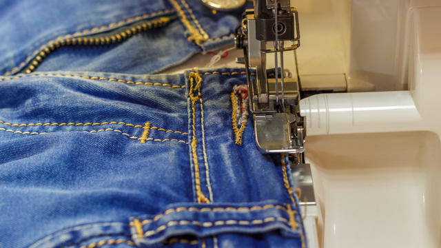 Sewing machine repair jeans trousers, close-up.