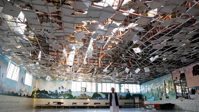 An Afghan man inspects a damaged wedding hall after a blast in Kabul, Afghanistan