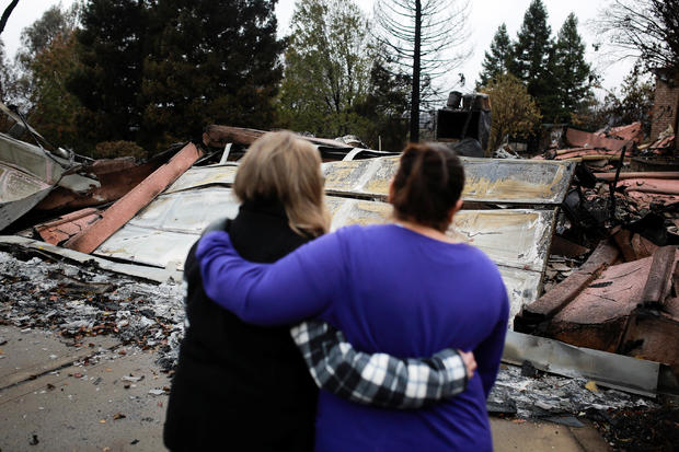 Irma Corona comforts neighbor Gerryann Wulbern in front of the remains of Wulbern's home after the two returned for the first time since the Camp Fire in Paradise