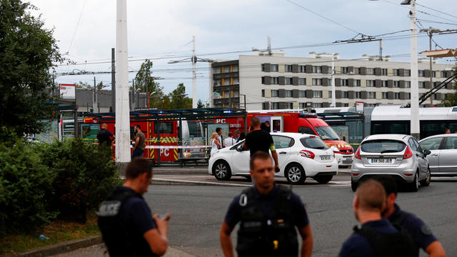 French police secure the area after one person was found dead and six others wounded in a suspected knife attack in Villeurbanne, near Lyon