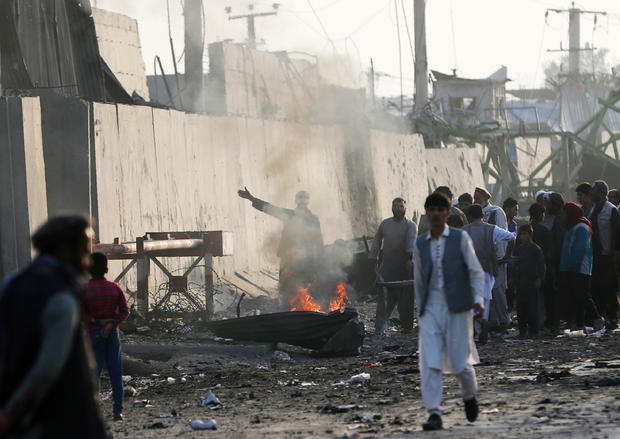 Angry Afghan protesters burn tires and shout slogans at the site of a blast in Kabul, Afghanistan