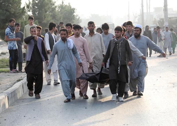 Afghan men carry the dead body of a civilian at the site of a blast in Kabul