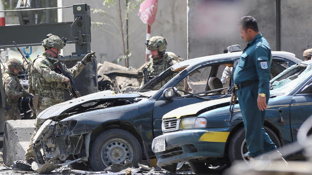 Foreign troops with NATO-led Resolute Support Mission investigate at the site of a suicide attack in Kabul