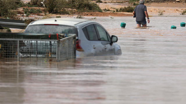 A man wades through a flooded street after heavy rains in San Javier