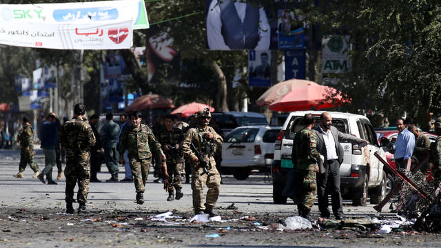 Afghan security forces remove the remains of bodies from the site of a blast in Kabul