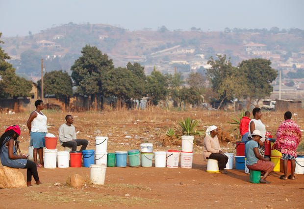 Locals wait for their turn to collect water from a borehole in Warren Park, Harare