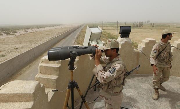 An Iranian border guard looks through a