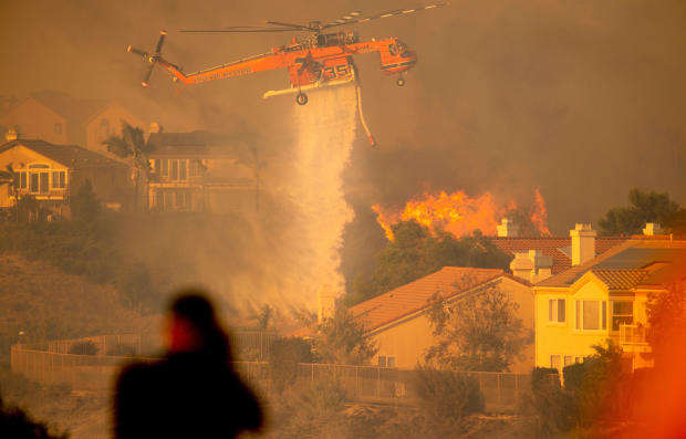 A helicopter drops water to help fight the Saddle Ridge Fire in the Porter Ranch section of Los Angeles, California, on October 11, 2019.
