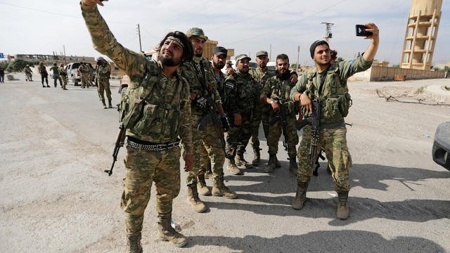 FILE PHOTO: Turkey-backed Syrian rebel fighters take pictures with mobile phones at the border town of Tel Abyad
