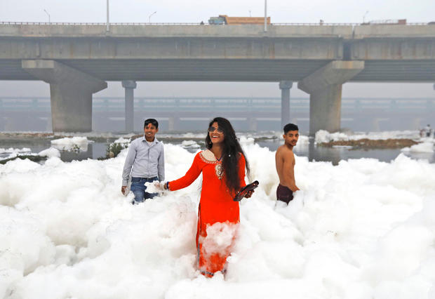 People posing for photos while standing in the foam covering the polluted Yamuna River on a blurred morning in New Delhi