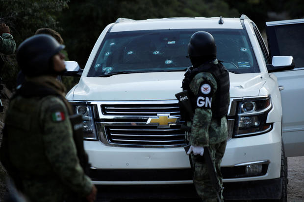 Soldiers assigned to Mexico's National Guard stand by a bullet-riddled vehicle belonging to one of the Mexican-American Mormon families that were killed by unknown assailants, in Bavispe